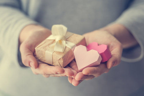Hands holding small paper gift box and two paper valentine's hearts. Toned picture