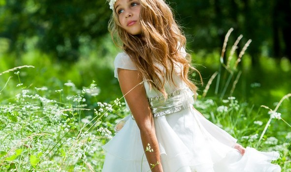 Cute girl holding white dress in green field.